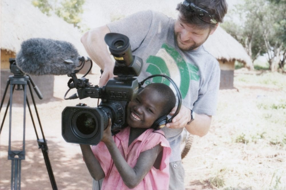 Steve and a child in Africa playing with a large camera